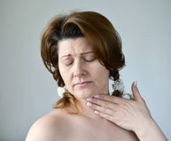 Adult woman with a sore throat on ight background Stock Photography