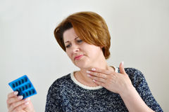 Adult woman with a sore throat. On a light background Stock Image