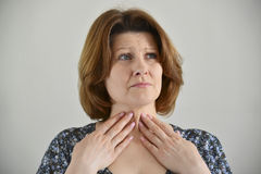 Adult woman with a sore throat on  light background. Adult woman with a sore throat on a light background Royalty Free Stock Photography