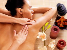 Adult woman in spa salon having body massage. Stock Photography