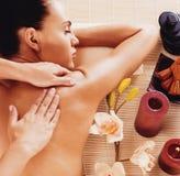 Adult woman in spa salon having body massage. Stock Photography
