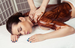 Adult woman in spa salon having body relaxing massage, lying on Stock Images