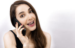 Adult woman speaking with mobile. Woman speaking with a mobile phone isolated over white background Royalty Free Stock Photography