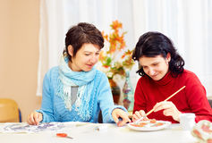 Adult woman with special needs are engaged in handcraft in rehabilitation center. Happy adult women with special needs are engaged in handcraft in rehabilitation Stock Photo