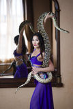 Adult woman in stage costume performs with big snake Royalty Free Stock Images