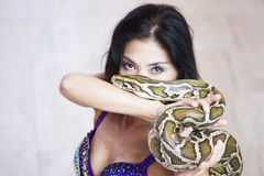 Adult woman in stage costume performs with big snake Stock Images
