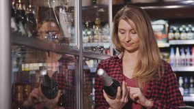 Adult woman standing in supermarket with bottle of alcohol in ha. Concentrated and focused adult woman in casual checkered shirt clothes choosing items in stock video
