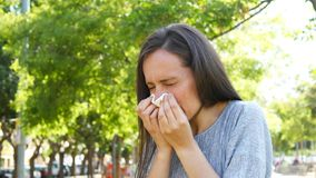 Adult woman sneezing in a park stock footage