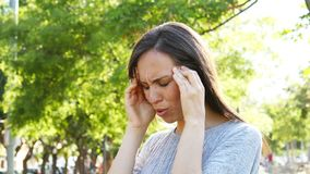Adult woman suffering migraine in a park. Adult woman complaining suffering migraine in a park stock video footage