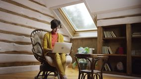 Adult woman surfing the Internet on laptop sitting in chair. On attic stock footage