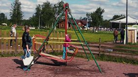 Adult woman sway little girl on big swing in summer day. Childhood. Summer event stock video