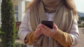 Adult woman is swiping over smartphone screen outdoors on city street, close-up stock footage
