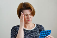 Adult woman taking a pill for  headache Royalty Free Stock Image