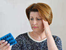 Adult woman taking a pill for  headache Royalty Free Stock Photography