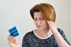 Adult woman taking a pill for  headache Stock Image