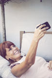 Adult woman taking a self portrait with mobile phone. Happy adult woman taking a self portrait with mobile phone Royalty Free Stock Photos