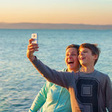 Adult woman taking a selfie with teenager boy. With a white smart phone, with lake in the background Royalty Free Stock Photography