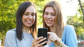 Adult woman and teen checking smart phone. Happy adult woman and teenage girl checking smart phone in a park stock video