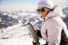 Adult woman with thermos on mount top with spectacular view of snowy mountains on background stock photo