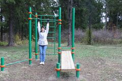 Adult woman training on a horizontal bar. Adult woman in a white jacket training on a horizontal bar on a street sports field in the autumn forest Stock Photo