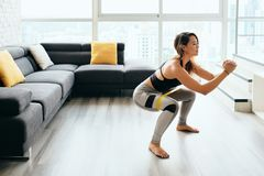 Adult Woman Training Legs Doing Side Squat at Home royalty free stock photo