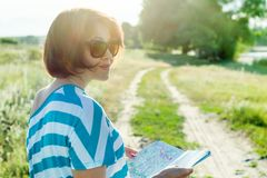 Adult woman traveler looking into the tourist map in the rural road. Stock Photo