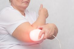An adult woman treats the elbow joint with a magnetic field, relieves pain and inflammation with a medical magnet, physiotherapy. Copy space, bursitis stock photography