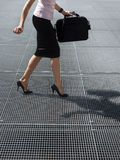 Adult woman trying to balance on high heels shoes. Cropped view of mid adult business woman walking on high heels, trying to balance on grating Royalty Free Stock Image