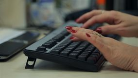 Adult woman typing on black keyboard. Close up. Adult woman typing on black keyboard in office stock video footage