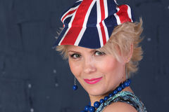 Adult woman in union jack cap. Pretty Adult woman in union jack hat on blue background Royalty Free Stock Image