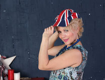 Adult woman in union jack cap. Pretty Adult woman hold visor of union jack cap Stock Photo