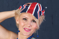 Adult woman in union jack cap. Pretty Adult woman hold visor of union jack cap Stock Image