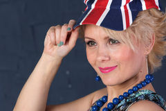 Adult woman in union jack cap. Pretty Adult woman hold visor of union jack cap Royalty Free Stock Images