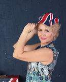 Adult woman in union jack cap. Pretty Adult woman hold visor of union jack cap Stock Photos