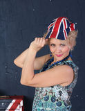Adult woman in union jack cap. Pretty Adult woman hold visor of union jack cap Royalty Free Stock Photos