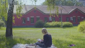 Adult woman uses digital tablet relaxing on blanket in park. Young woman is relaxing on blanket in park and uses digital tablet. The female enjoys warm weather stock footage