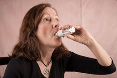 Adult Woman using an Inhaler. A senior woman uses an inhaler, a medical device used for delivering medication into the body via the lungs most commonly used for stock images