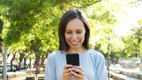 Adult woman using smart phone in a park stock footage