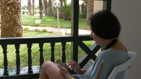 Adult woman using smartphone while summer resting on outdoor balcony. Modern woman looking travel blog in mobile phone.  stock video footage
