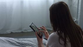 Adult woman using tablet pc sitting on the bed. Relaxed adult long hair woman with digital tablet surfing the net and drinking a mug of hot coffee while sitting stock video
