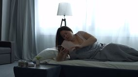 Adult woman waking up with mobile alarm clock stock footage