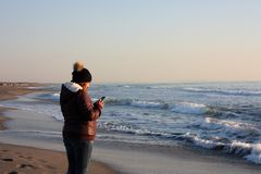 Adult woman walks by the sea, on the shoreline, checking her cell phone royalty free stock image