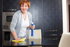 Adult woman washing glass table Royalty Free Stock Photos