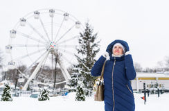 Adult woman wearing blue hooded coat enjoying strolling in winter amusement park outdoors. Nature cold season freshness concept. Full length portrait Stock Image