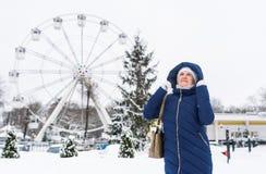 Adult woman wearing blue hooded coat enjoying strolling in winter amusement park outdoors. Stock Image