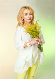 Adult woman in a white blouse with cute smiles and holding yellow flowers. Royalty Free Stock Image