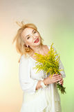 Adult woman in a white blouse with cute smiles and holding yellow flowers. Royalty Free Stock Photos