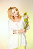 Adult woman in a white blouse with cute smiles and holding a yellow sunflower. Stock Photo