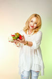 Adult woman in a white blouse and torn jeans smiling and holding vegetables. Royalty Free Stock Photo
