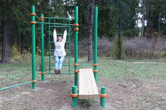 Adult woman in a white jacket training on a horizontal bar. On a street sports field in the autumn forest Royalty Free Stock Photos